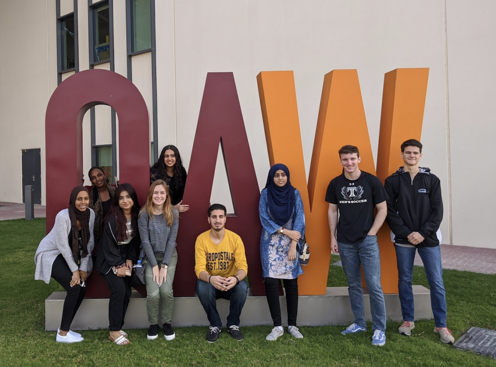 Students standing in front of a QAW statue